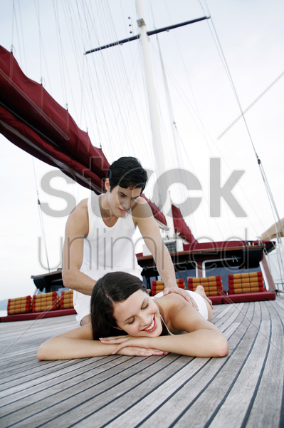 woman getting a body massage from her boyfriend stock photo