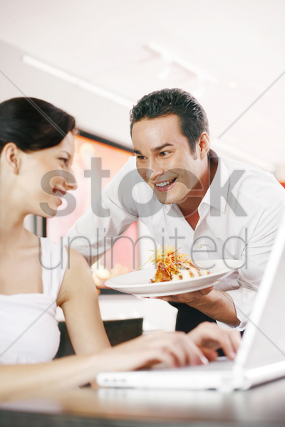 woman getting a delicious dish from her boyfriend while using laptop stock photo