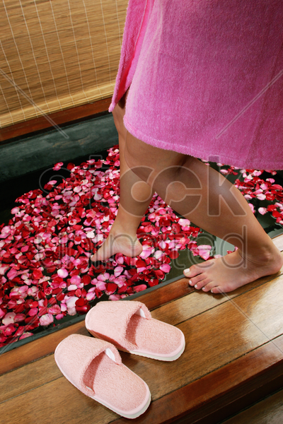 woman getting into a flower bath stock photo