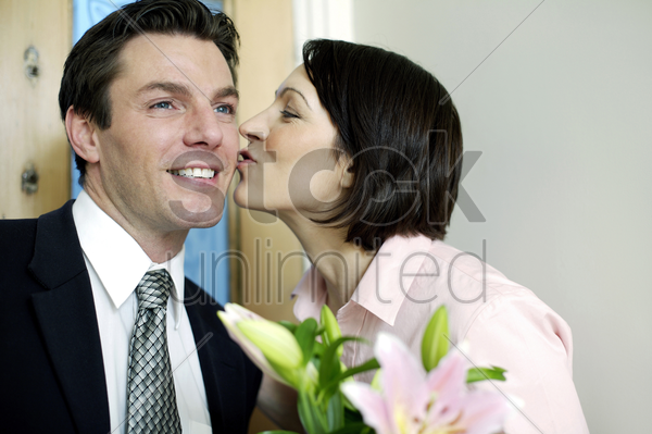 woman giving her husband a peck on the cheek stock photo