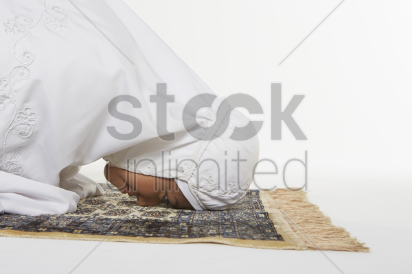 woman going down to the floor and prostrate by pressing forehead, placing palms, knees and pads of the toes on the floor stock photo