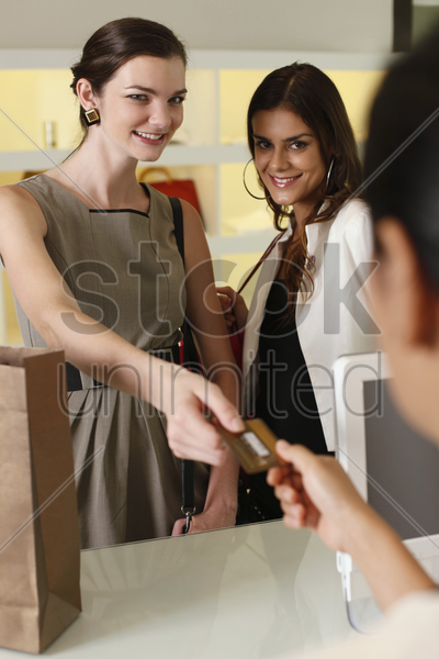 woman handing credit card to cashier while her friend looks on stock photo