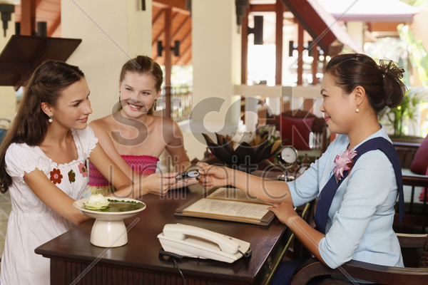 woman handing credit card to customer service representative stock photo