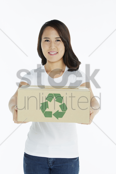 woman handing out a cardboard box stock photo