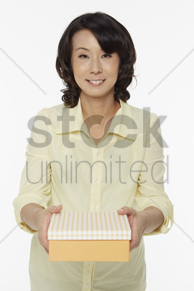 woman handing out a gift box stock photo