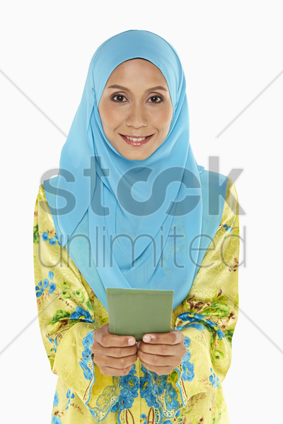 woman handing out a green packet stock photo