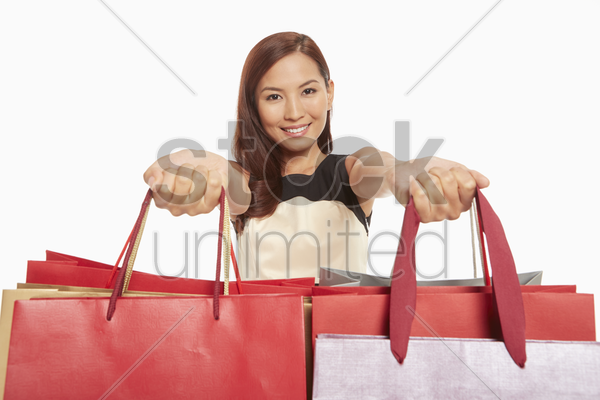 woman handing out shopping bags stock photo