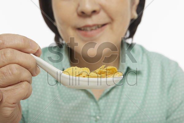 woman having cereals for breakfast stock photo