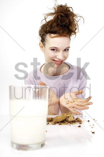 woman having cookies and a glass of milk for breakfast stock photo