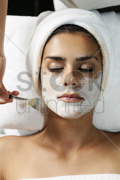 woman having facial mask applied with brush stock photo