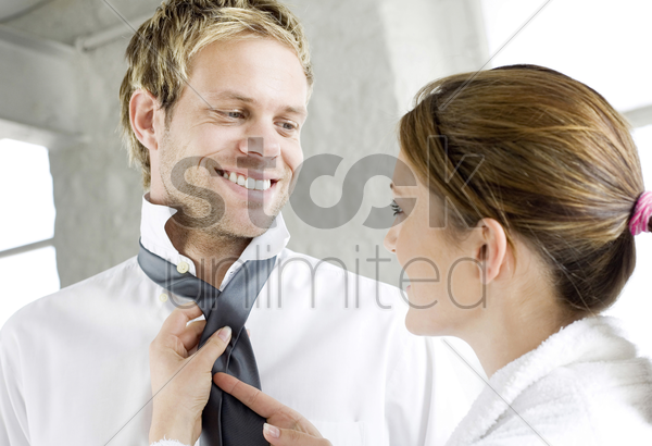 woman helping her husband with his tie stock photo