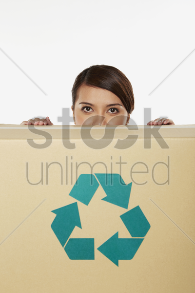 woman hiding behind a recyclable cardboard box stock photo