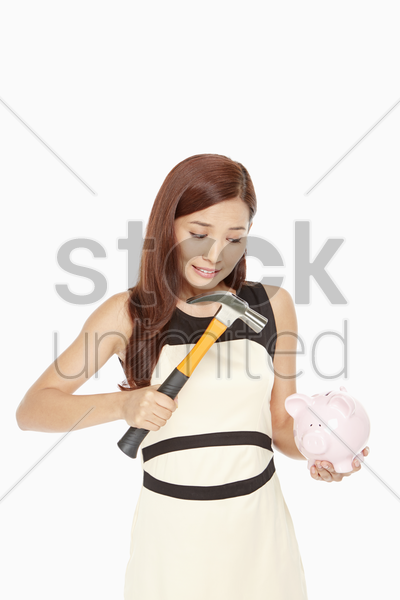 woman hitting a piggy bank hammer stock photo