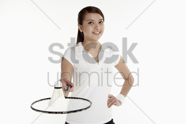 woman holding a badminton racket with shuttlecock placed on it stock photo