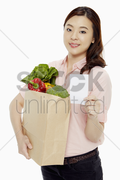 woman holding a bag of groceries and a shopping list stock photo