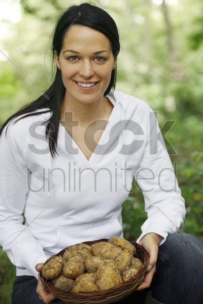 woman holding a basket of potatoes stock photo
