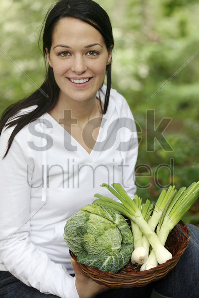 woman holding a basket of vegetables stock photo