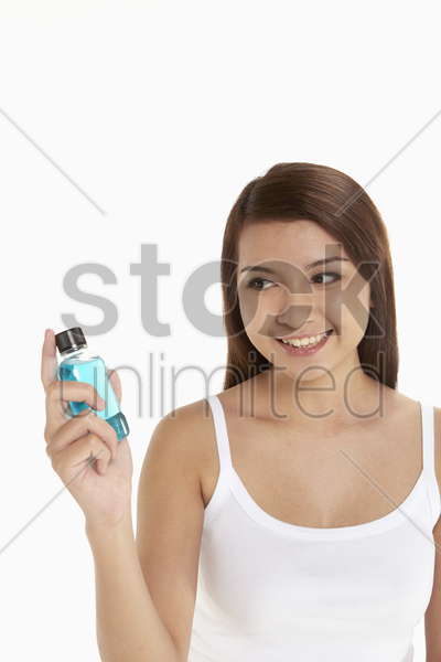 woman holding a bottle of mouth wash stock photo