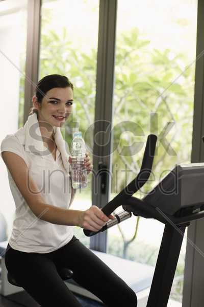 woman holding a bottle of water while exercising in the gymnasium stock photo