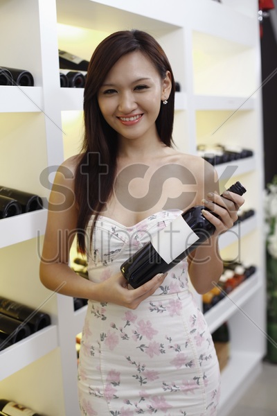 woman holding a bottle of wine stock photo