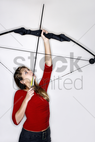 woman holding a bow and an arrow stock photo