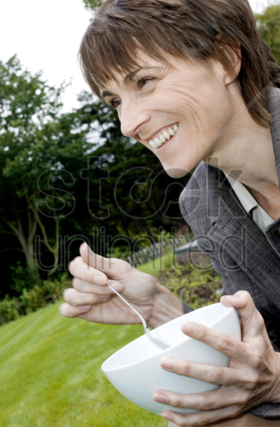 woman holding a bowl and a spoon stock photo