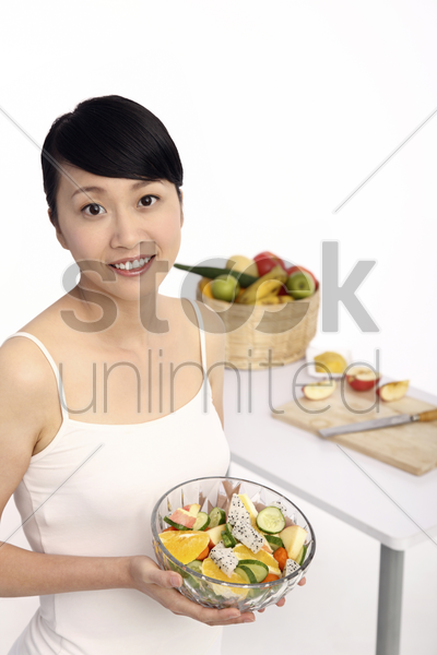 woman holding a bowl of fruit salad stock photo