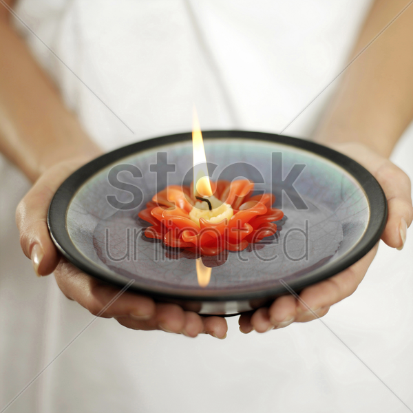 woman holding a bowl of water with lit candle floating on it stock photo