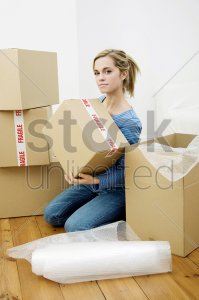 woman holding a box while looking at the camera stock photo
