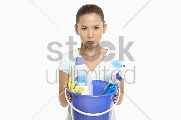 woman holding a bucket filled with cleaning supplies stock photo