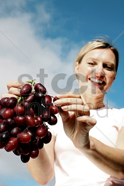 woman holding a bunch of grapes stock photo
