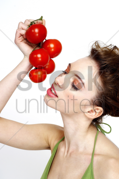woman holding a bunch of tomatoes stock photo
