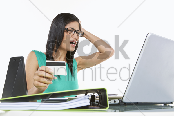 woman holding a credit card, looking frustrated stock photo