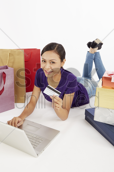 woman holding a credit card while using laptop stock photo