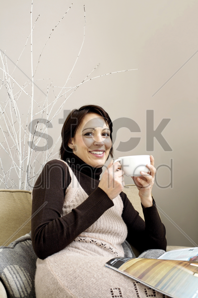 woman holding a cup of coffee with magazine on her lap stock photo