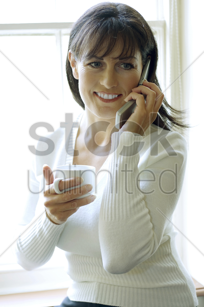 woman holding a cup while talking on the phone stock photo