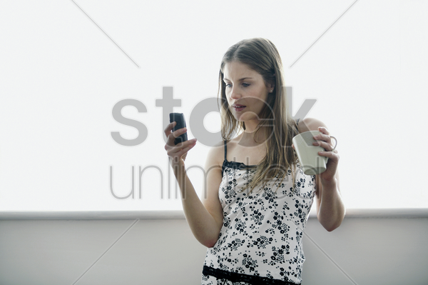 woman holding a cup while text messaging on the phone stock photo