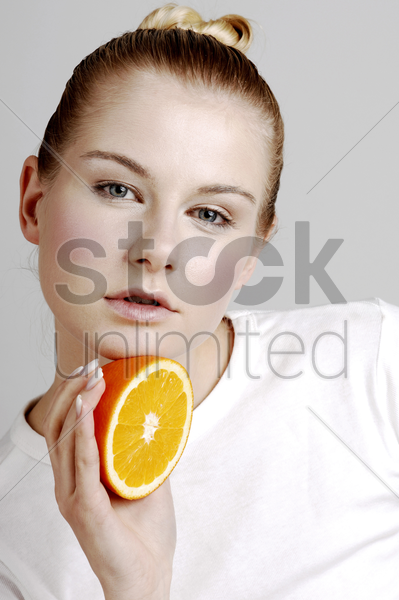 woman holding a cut orange stock photo