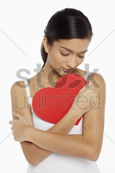 woman holding a cut out heart shape stock photo