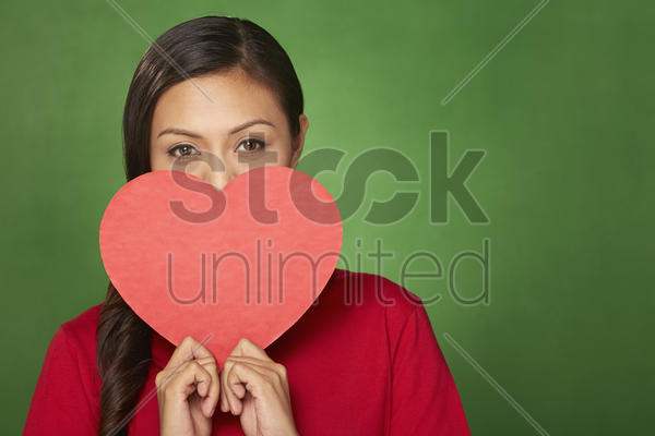 woman holding a cut out heart stock photo