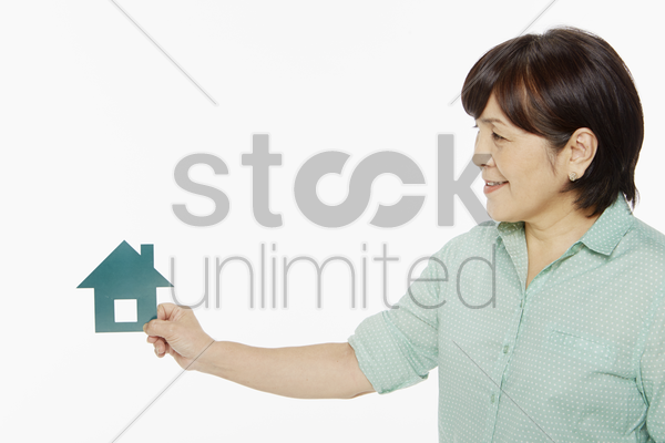 woman holding a cut out house stock photo