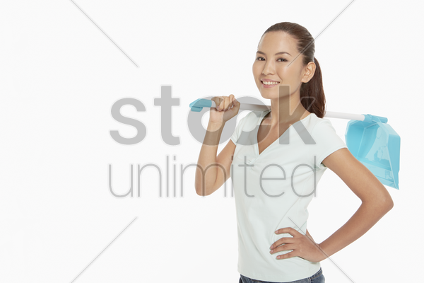 woman holding a dustpan, smiling stock photo