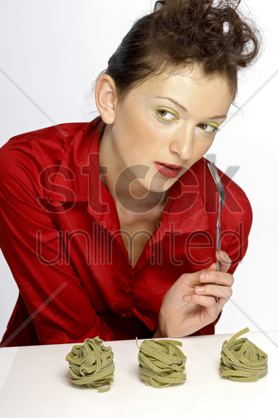 woman holding a fork with coloured pasta on the table stock photo