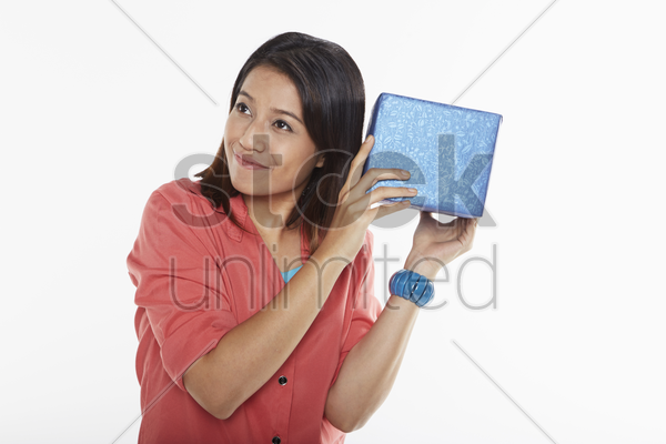 woman holding a gift box close to her ears stock photo