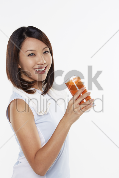 woman holding a glass of carrot juice stock photo
