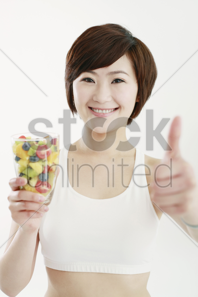 woman holding a glass of mixed fruits and showing thumbs up stock photo