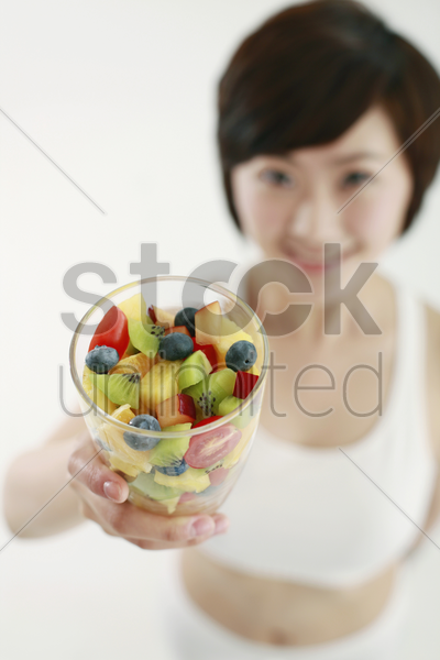 woman holding a glass of mixed fruits, focus on foreground stock photo