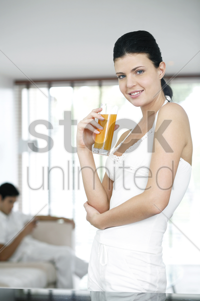 woman holding a glass of orange juice while smiling at the camera stock photo