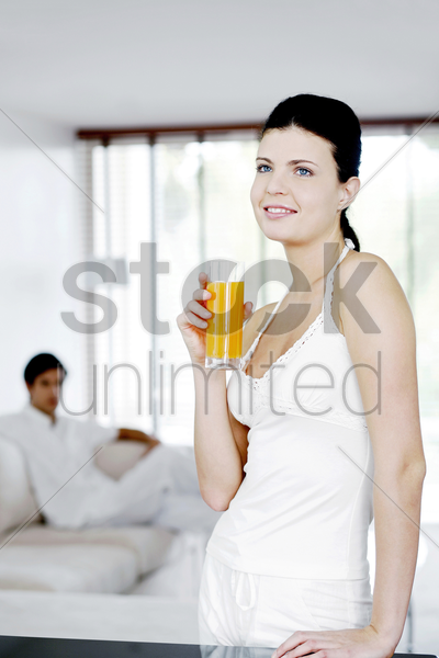 woman holding a glass of orange juice with her boyfriend sitting in the background stock photo