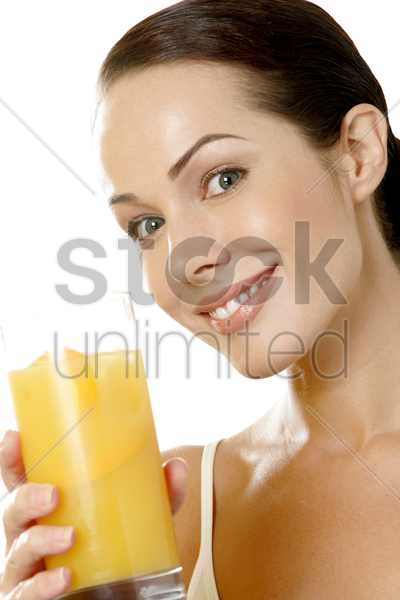 woman holding a glass of orange juice stock photo